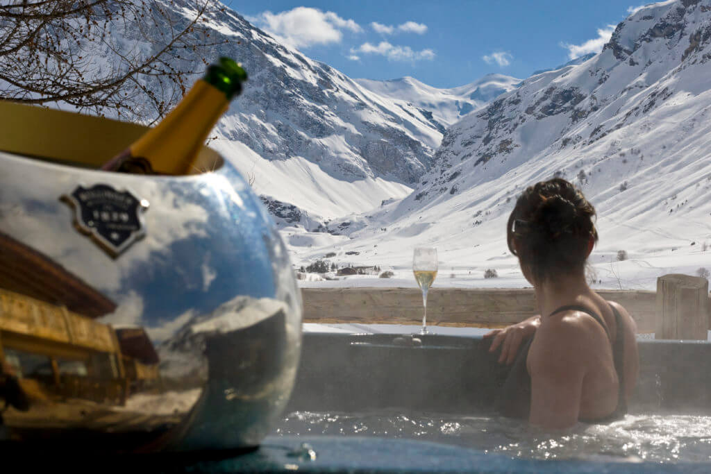 Alpine wedding guest enjoying the mountain views from the outdoor hot tub at Le Chardon Val d'Isere